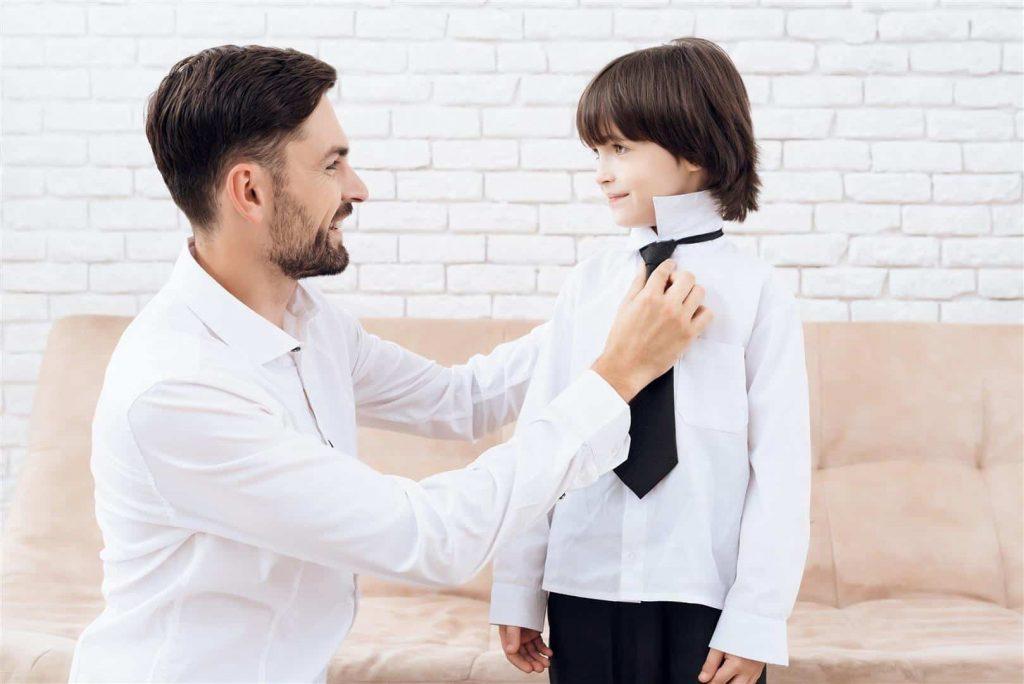 Far hjælper søn med at tage tøj på til konfirmation